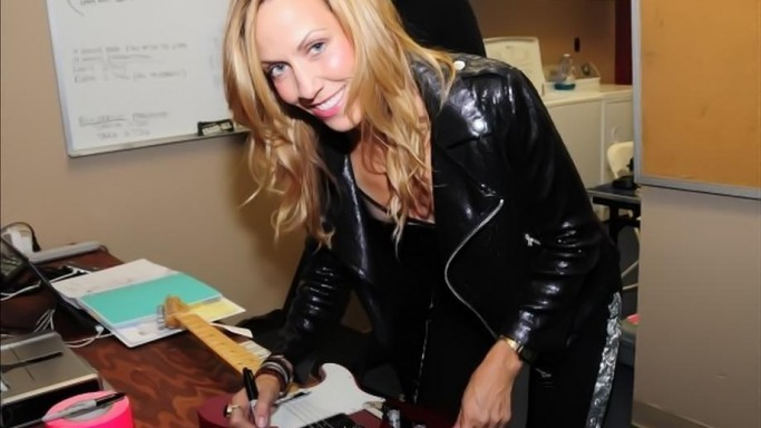 Sheryl Crows signs guitar at Tiger Woods Foundation event